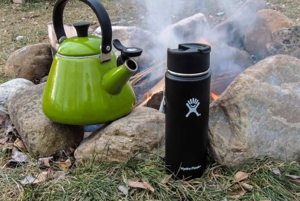 A green tea kettle over a campfire, next to a black Hydro Flask insulated travel mug.
