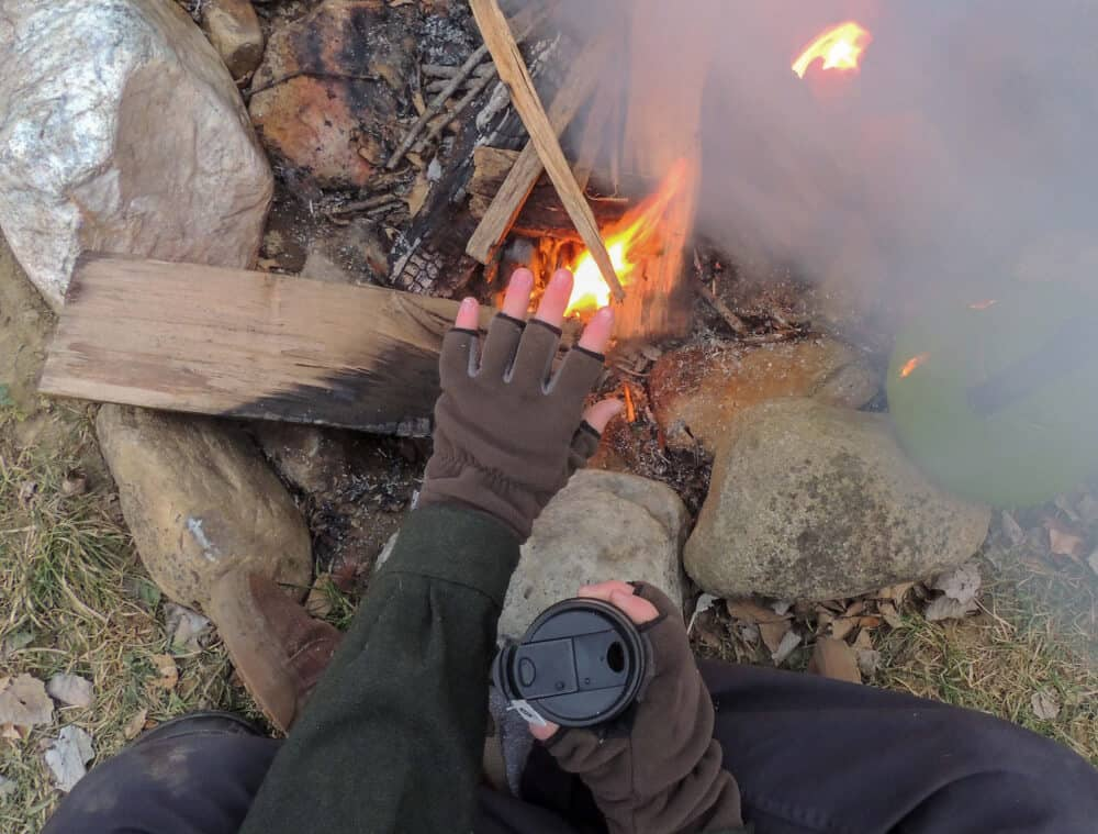 A campfire with a green kettle next to it. Someone is sitting next to the fire, but you can only see their hands and that they are holding a cup of camping coffee.