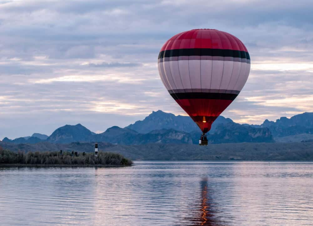 A red and white striped hot air balloon floating near the surface of Lake Havasu with mountains in the background.