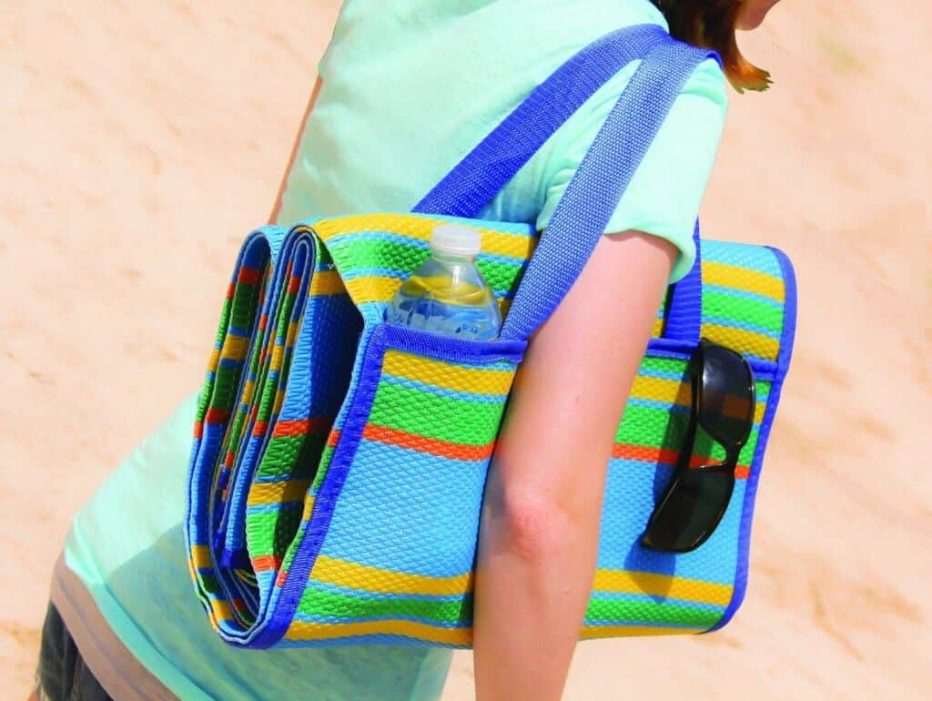 A women on the beach, carrying a colorful Camco mat.