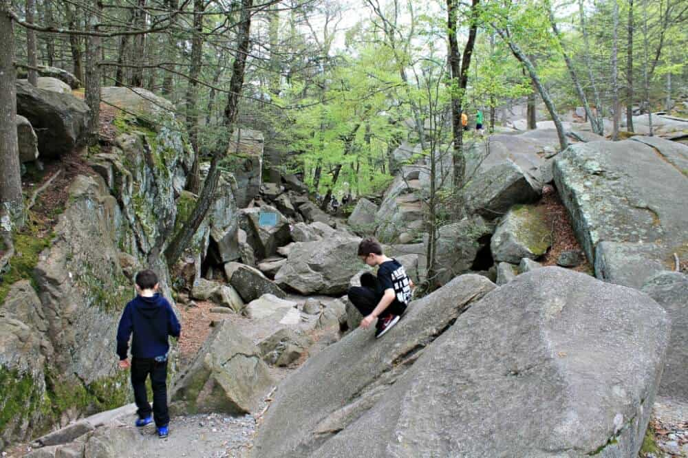 hikers walking and climbing around on boulders in Purgatory Chasm State Reservation