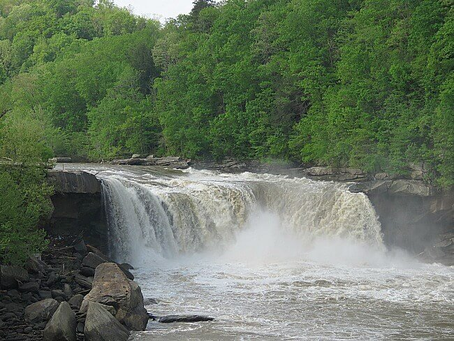 a scene of a waterfall with green trees behind it in Cumberland Falls State Resort Park