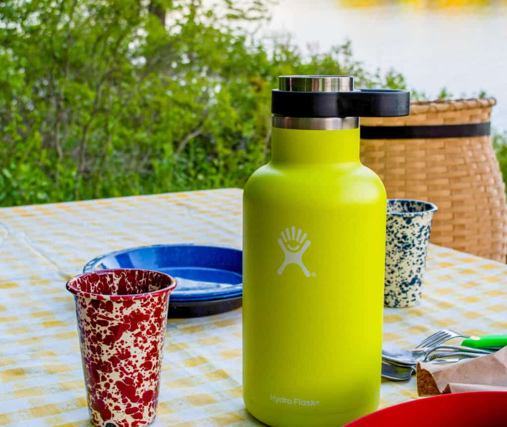 A water bottle and flatware sit upon a yellow checked tablecloth outside.