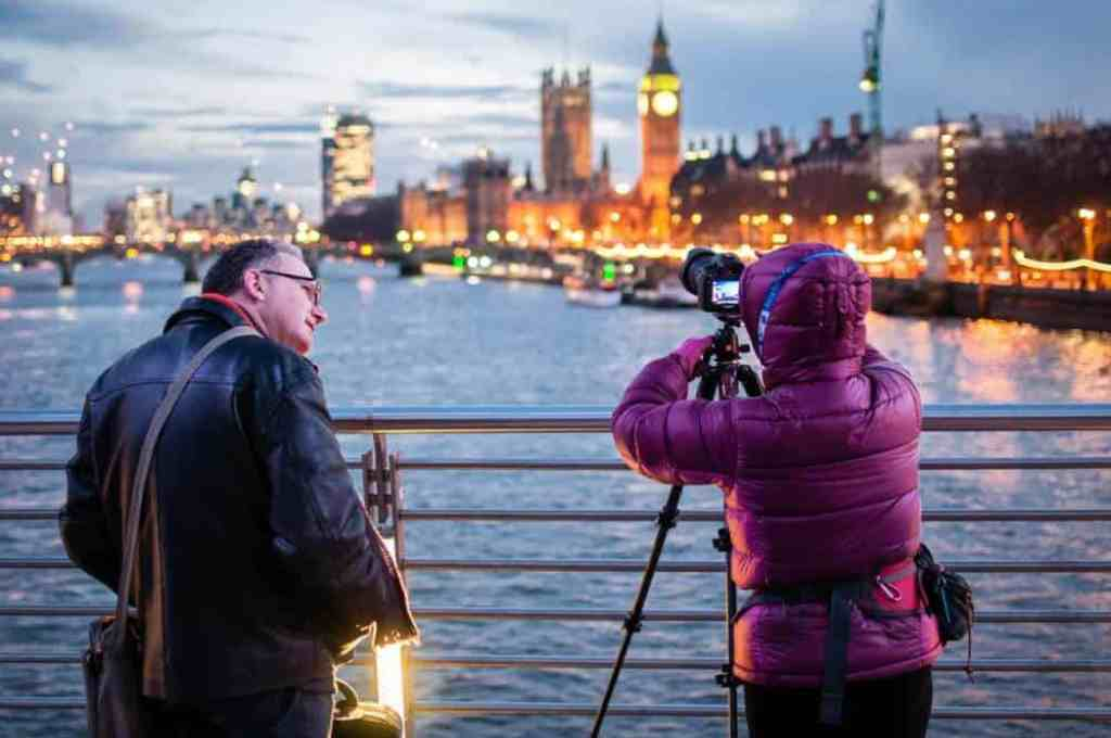 A woman looks through a camera toward down town London. A man looks on with a smile.