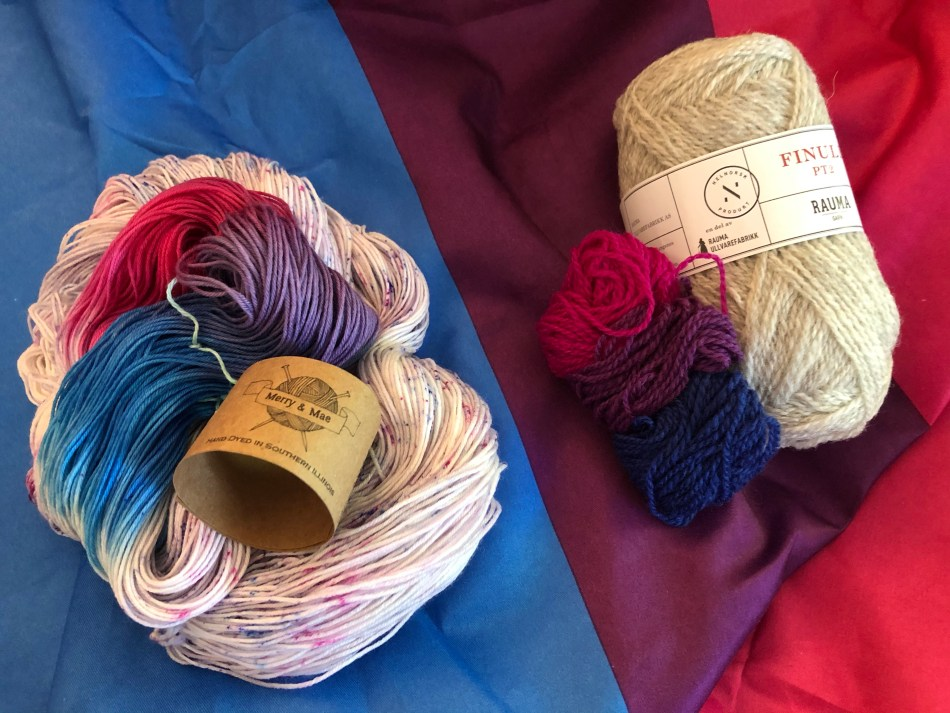 Two yarns with the bisexual pride flag colors (pink, purple, blue) sitting on a. bi pride flag.