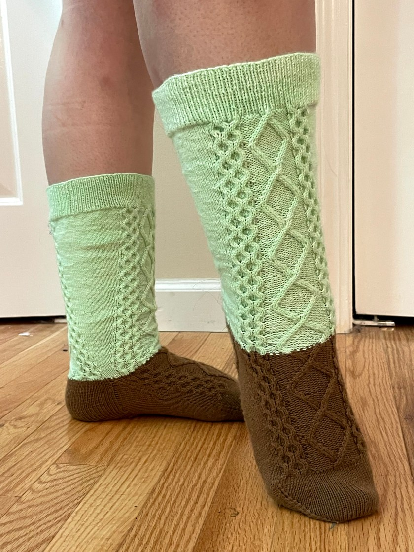 Green and brown socks with a diamond and honeycomb cable pattern.
