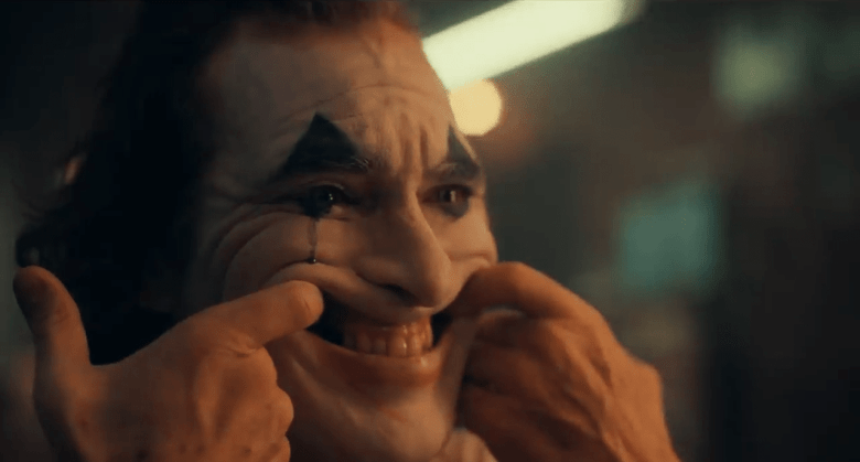Joker makes a smile with his fingers.
