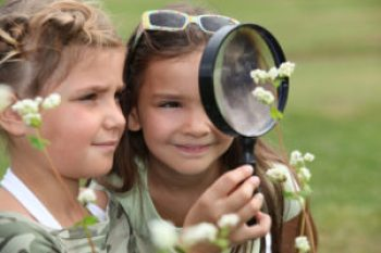 Two Little Girls With Magnifying Glasses
