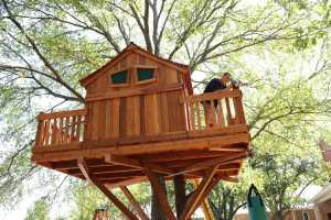 A man stands on the deck of his child's new Backyard Fun Factory custom redwood tree house and looks through the telescope. The tree house is built on a tree in his backyard and features a punching bag.