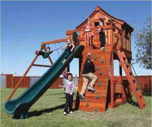 Kids playing in a redwood fort with a green slide, swings, a climbing wall and a small house on top.