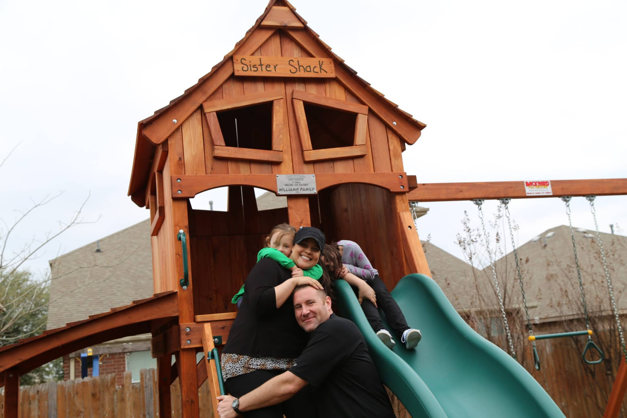 A picture of one of Backyard Fun Factory's Amazing Love Giveaway redwood playsets - featuring a fort, slides, swings, and, of course, the happy family.
