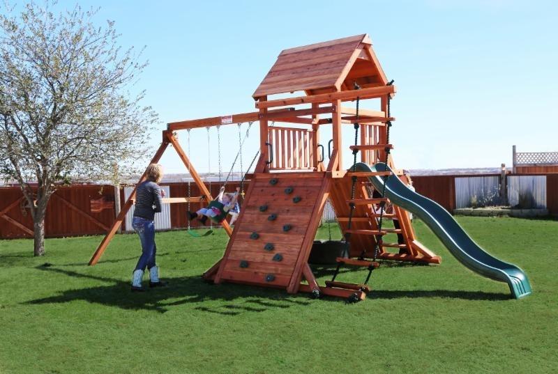 belt swings, ladder, playset, repel wall, rock wall, rustler, slide, swing set, tire swing, trapeze bar, wood roof, child, outdoor playset