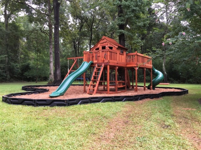 Large redwood tree deck with zip line and spiral slide. Front of playset is a cabin with front porch and swings on the side.