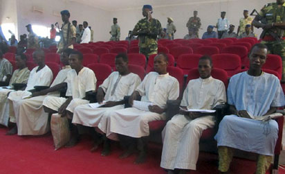 A picture taken on August 26, 2015 shows suspected members of Nigeria-based Islamist group Boko Haram sitting in court in N'Djamena, during the opening of the trial of ten suspected Boko Haram members. Ten suspected Boko Haram members went on trial in Chad on August 26 over their alleged roles in twin attacks that killed 38 people in the capital N'Djamena in June. AFP PHOTO / STRINGER