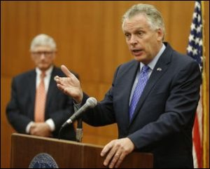 """Governor McAuliffe explains his plan to close budget shortfall this year. Secretary of Finance """"Ric"""" Brown stands in the background."""