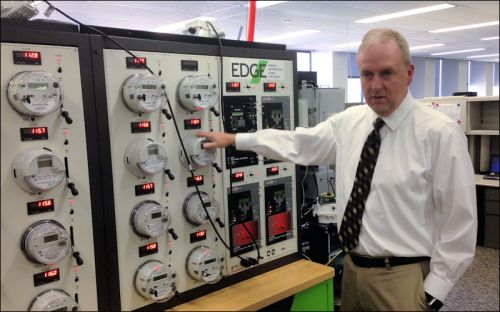 Todd Headlee, director of Dominion Voltage Inc., shows off the in-house electric circuit the company uses to model upgrades to its conservation voltage reduction system.
