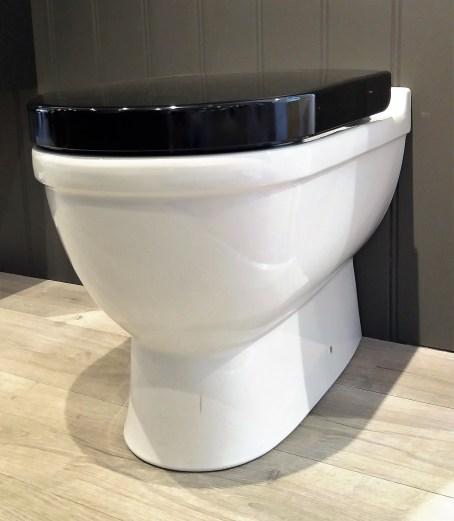 toalett med svart toalettsete