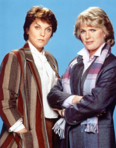 Two women (Cagney and Lacey) in 80s clothes (blazers, blouses and scarves) staring challengingly into the camera.