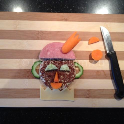 Stap 7: snij een veer van een wortel en maak van de restjes een neus. en mond