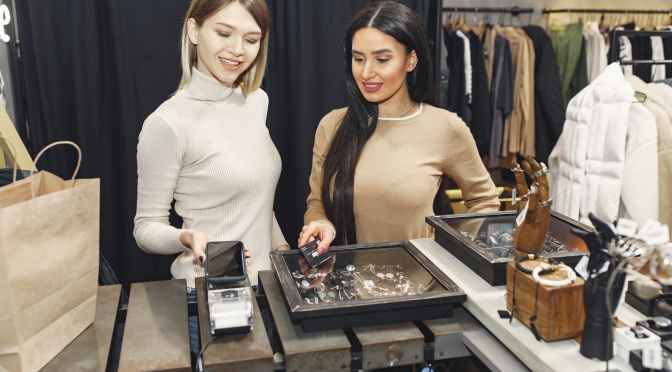 women paying for clothes with smartphone