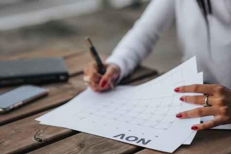 crop woman filling calendar for month