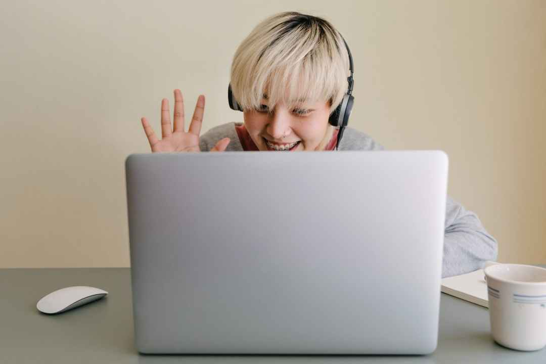 happy young woman having video call via laptop