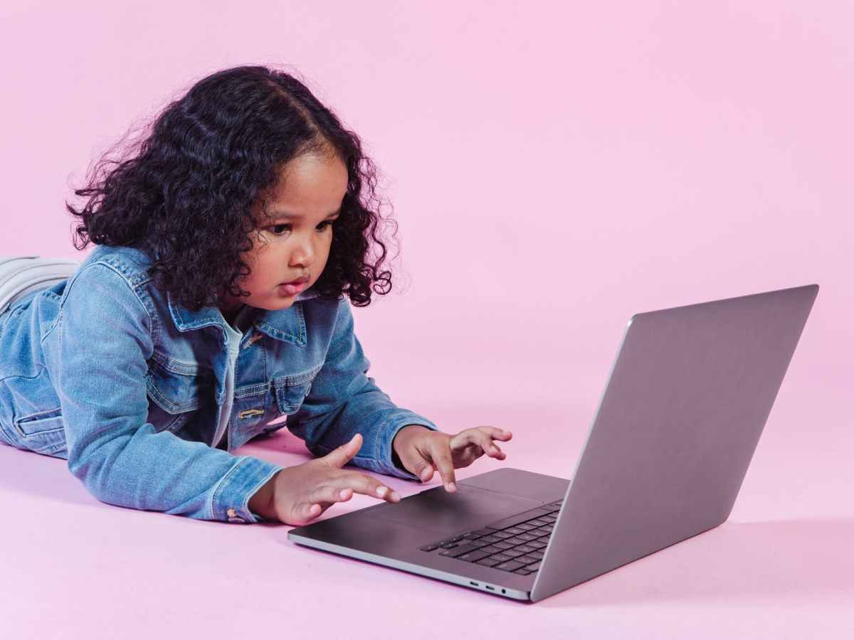 adorable black girl browsing laptop on floor