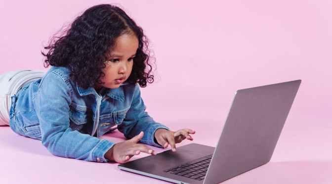 adorable black girl browsing laptop on floor