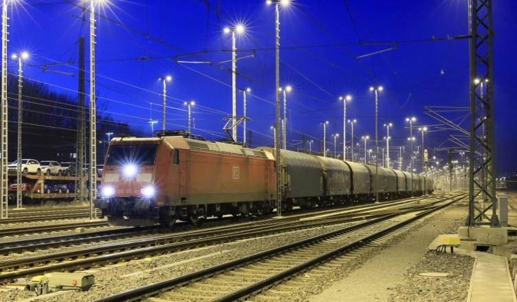 Eine Ellok der Baureihe 185 TRAXX steht im abendlichen Aachen West Gbf abfahrbereit mit einem Stahl-Coil-Zug aus Belgien. (Foto: © DB AG / Uwe Miethe)