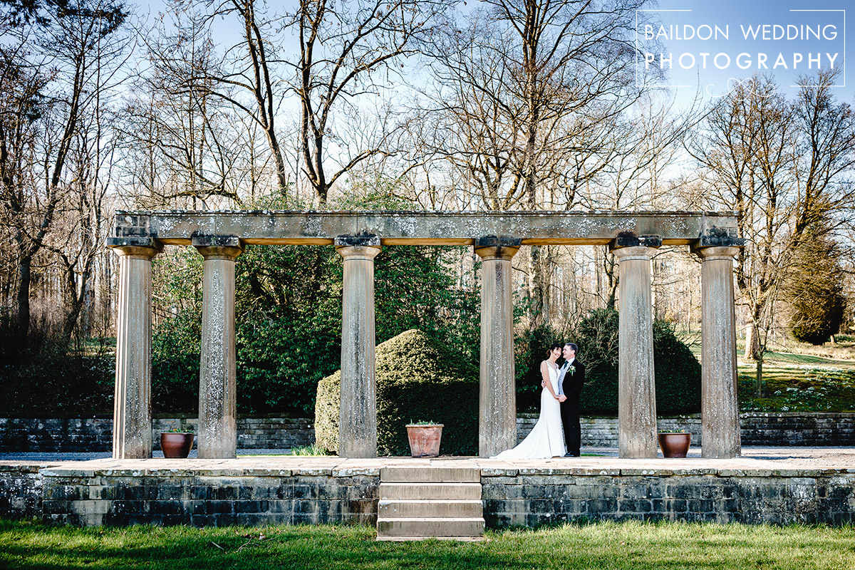 bride and groom stand amongst the ruins of the original house at the coniston hotel in skipton