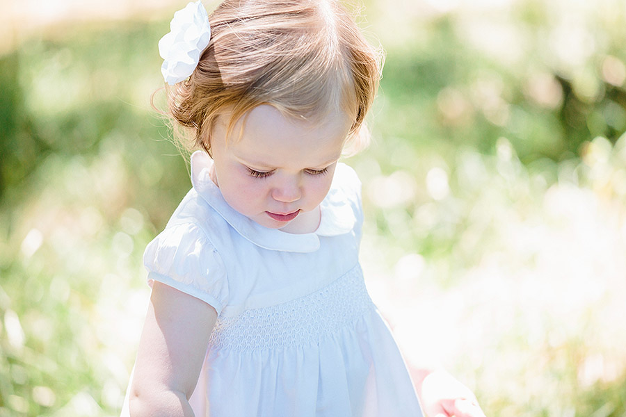 children's portrait taken in the sunshine on Shipley Glen. Little girl wear white dress with a flower in her hair