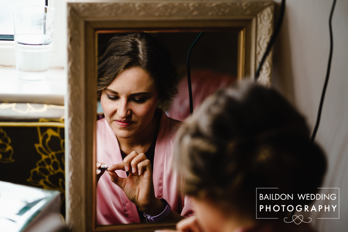 Bridesmaid puts on false lashes by the window light