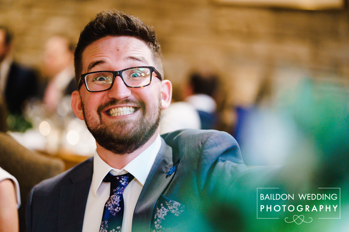 Cheesy smiles from male wedding guest
