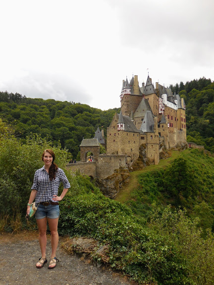 woman stands in front of Burg Eltz on a hilltop surrounded by trees