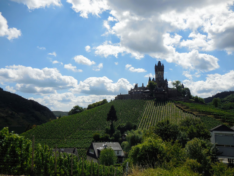Reichsburg Cochem sits atop a hill surrounded by vineyards and countryside