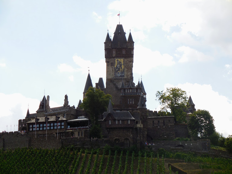 Reichsburg Cochem sits atop a hill covered in vineyards