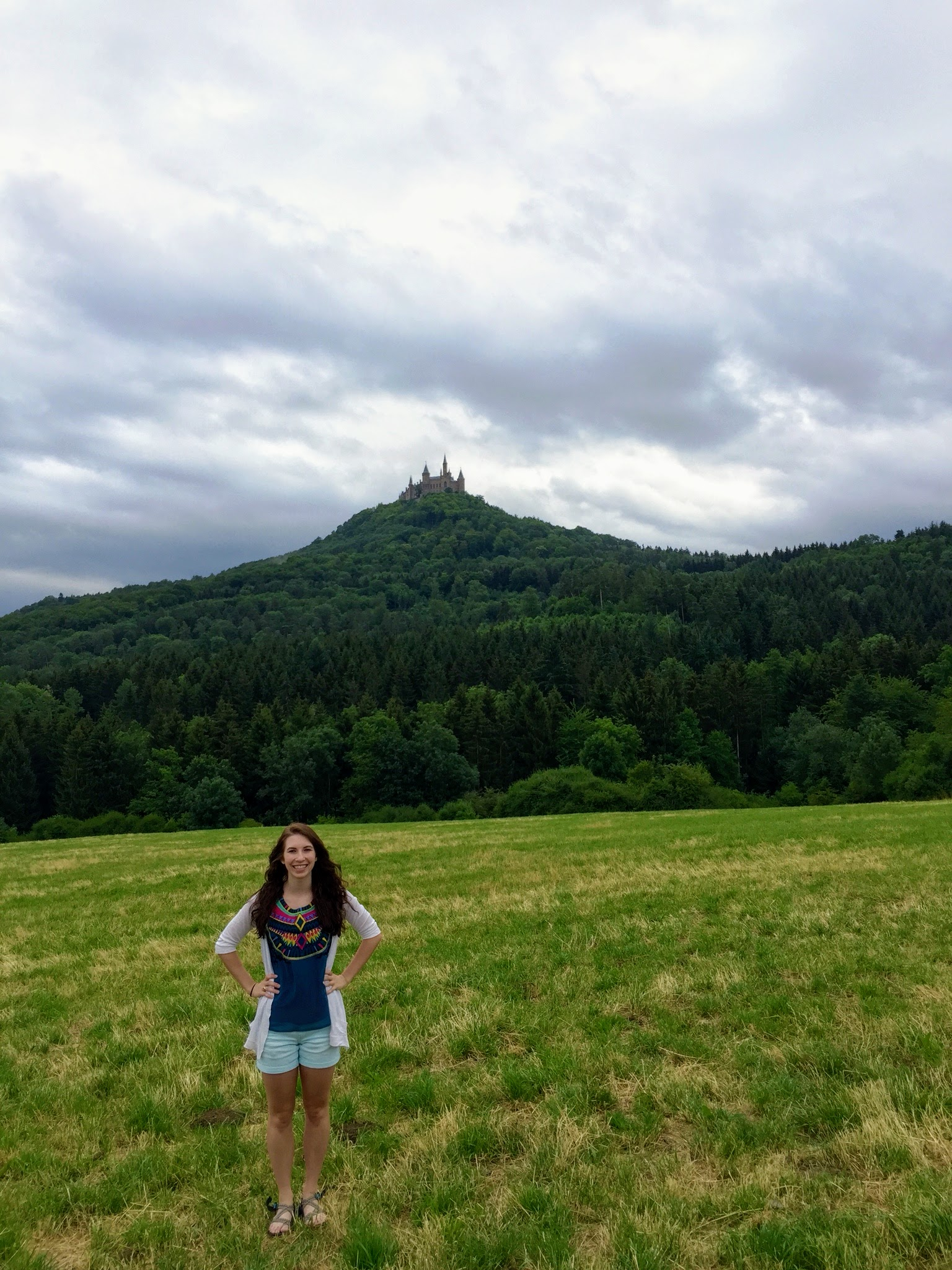 woman standing in a field in front of Burg Hohenzollern on a hill