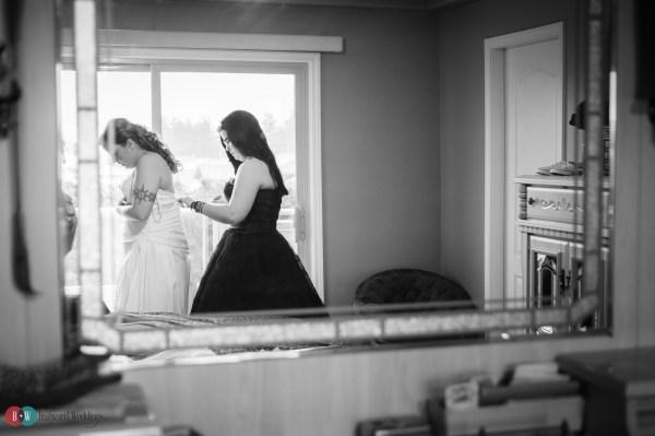 Bridesmaid getting bride ready in wedding dress