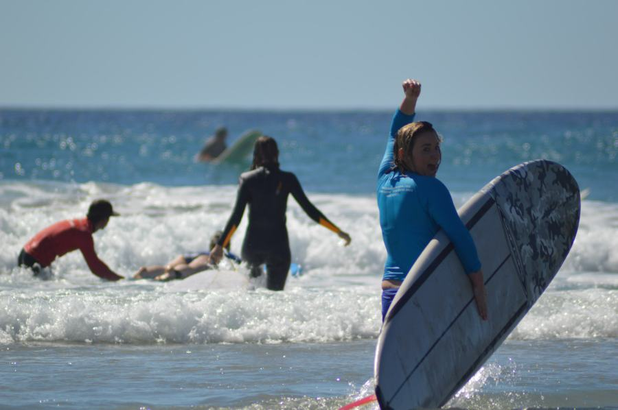 Girl learning to surf pumps her fist in the air