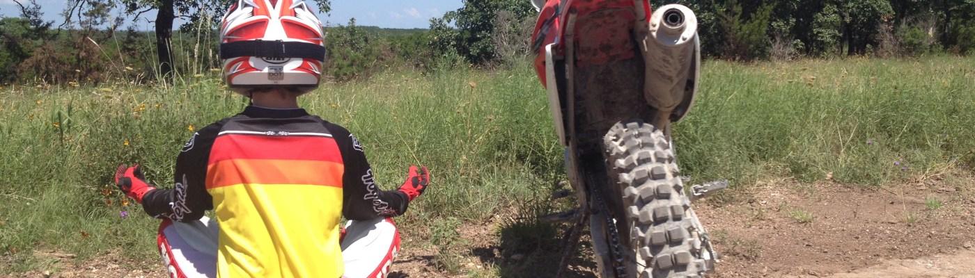 girl meditates next to dirt bike