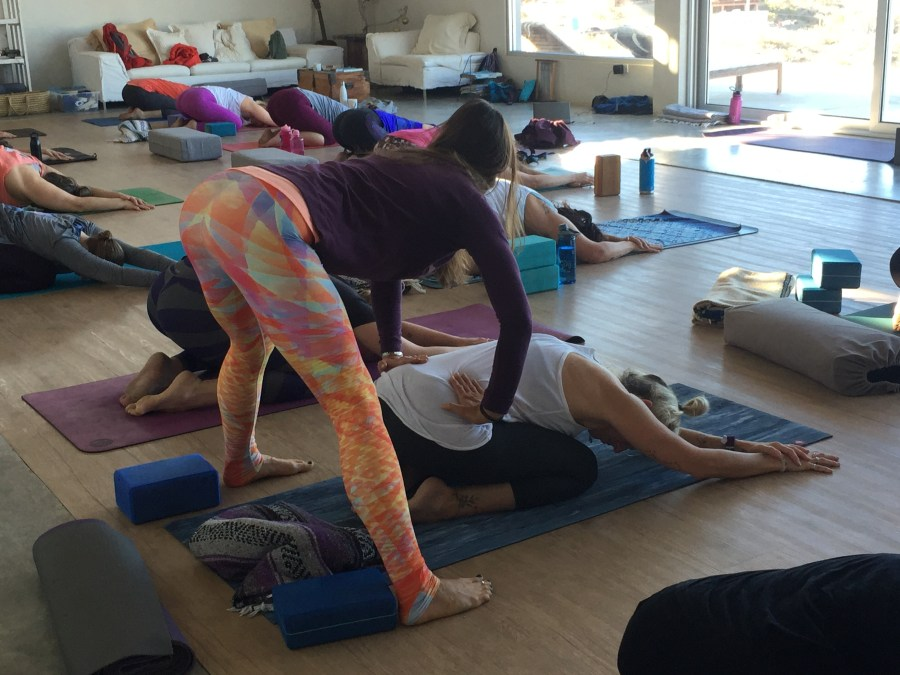 yoga teacher assisting a student