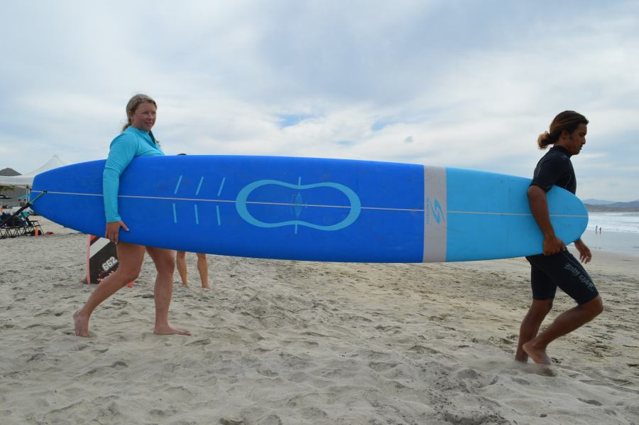 a surfer and her instructor carry a surfboard to the water