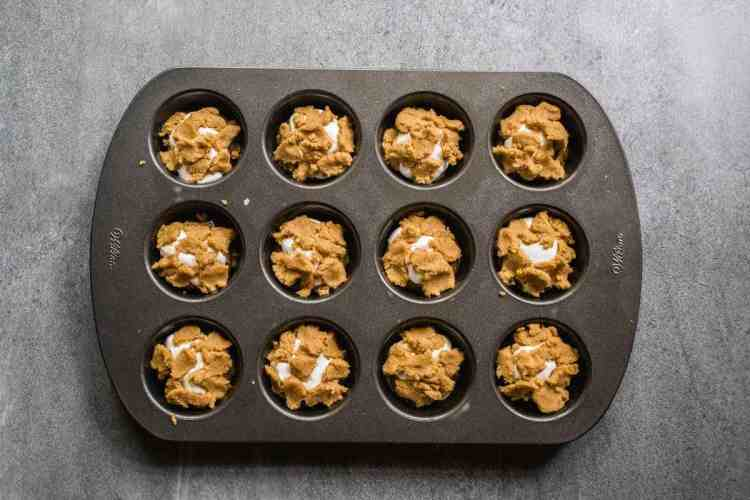 muffin tin with extra cookie dough crumbled on top the s'mores cookie cups