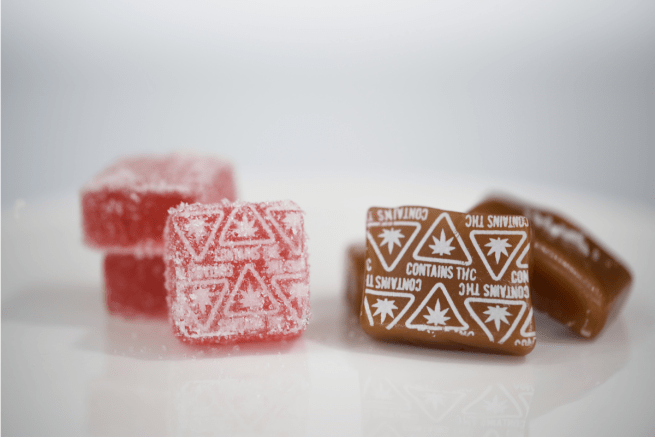 a caramel and gummy with massachusetts contains thc symbols in white embossed
