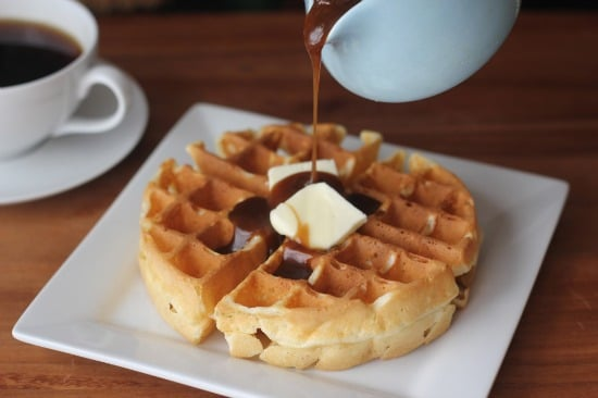 Upclose view of waffle with butter on top with syrup being poured on