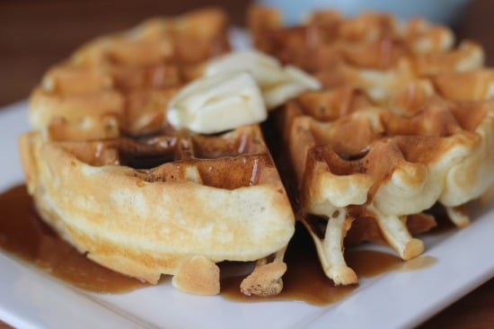 Upclose view of waffle with butter on top on a plate