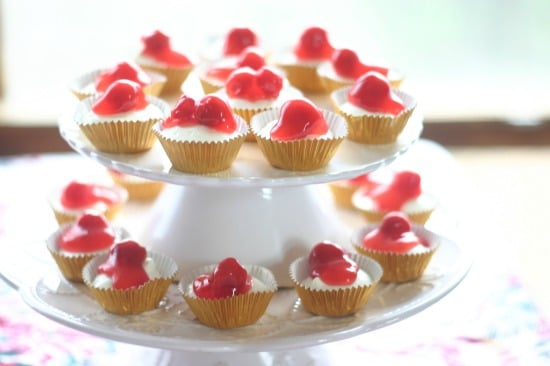 Mini cheesecakes in baking cups topped with cherries all on a 2 layer cake stand