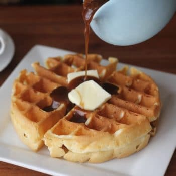 Waffle on a plate with butter and syrup being poured on
