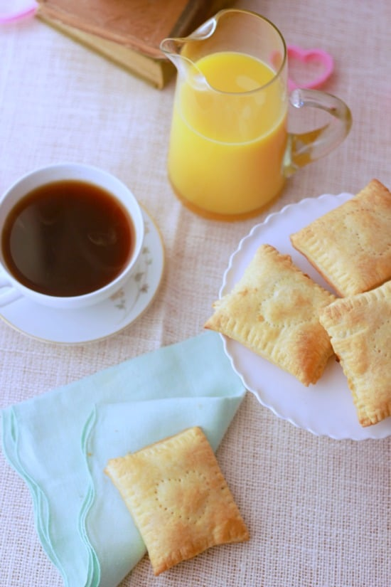 A top view of the breakfast pastries on a plate with a cup of coffee and orange juice on a tablecloth