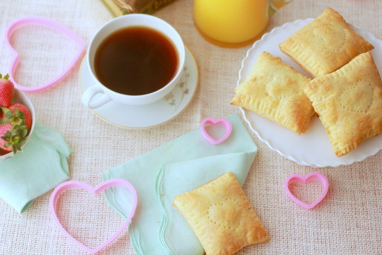 Pastries piled on a plate, coffee cup, orange juice, heart shaped cookie cutter, strawberries all on a tablecloth